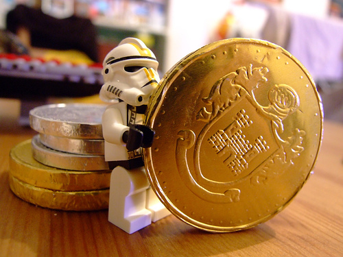 Lego stormtrooper holding huge chocolate coin.